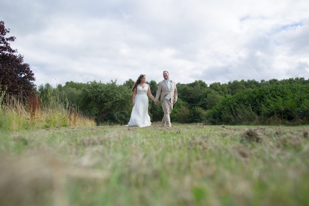 photo of bride and groom walking through field