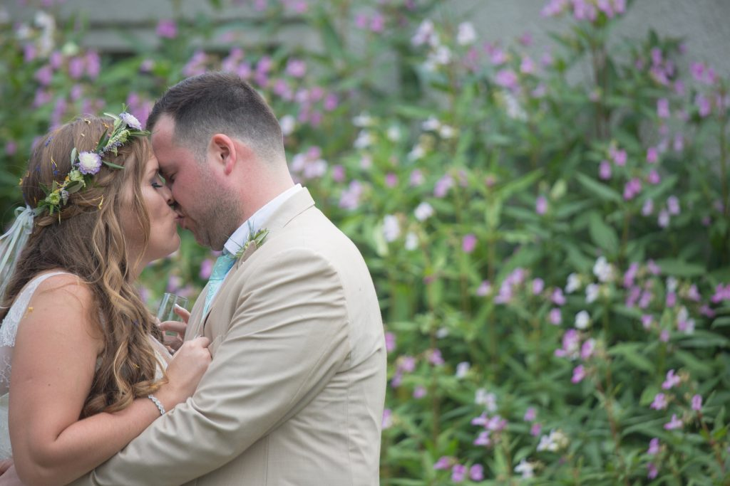 newly weds kissing with flowers in background