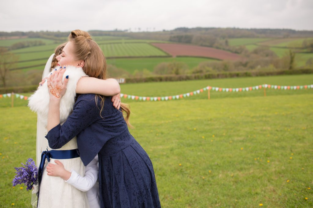 bride being hugged by bridesmaid