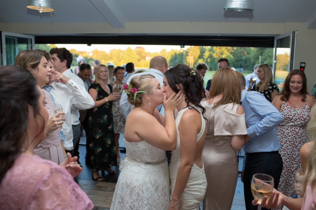two brides kissing at end of first dance