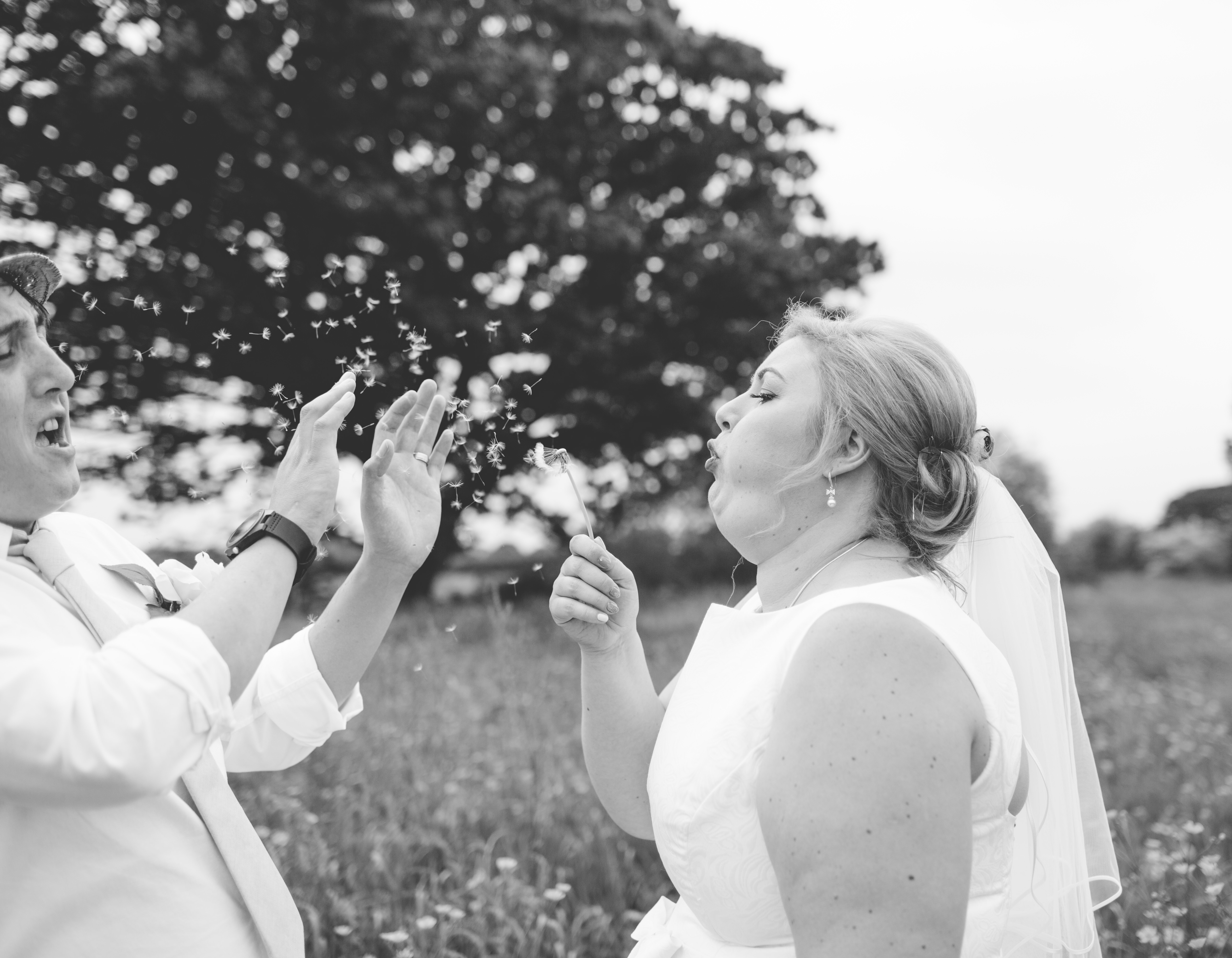black and white photo of bride blowing dandelion at husband