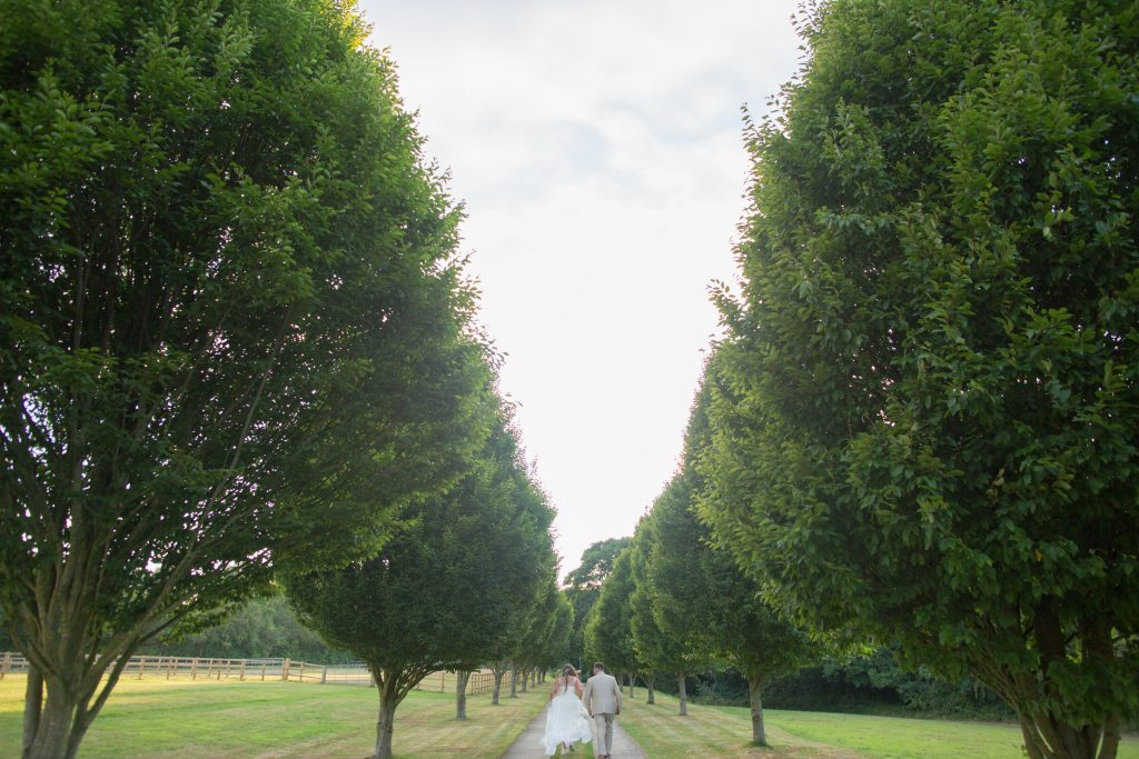 bride and groom walking down driveway of the holford estate