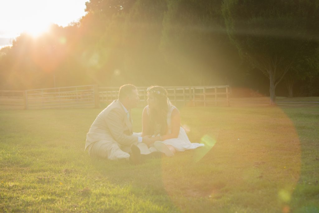 bride and groom sat on grass at sunset