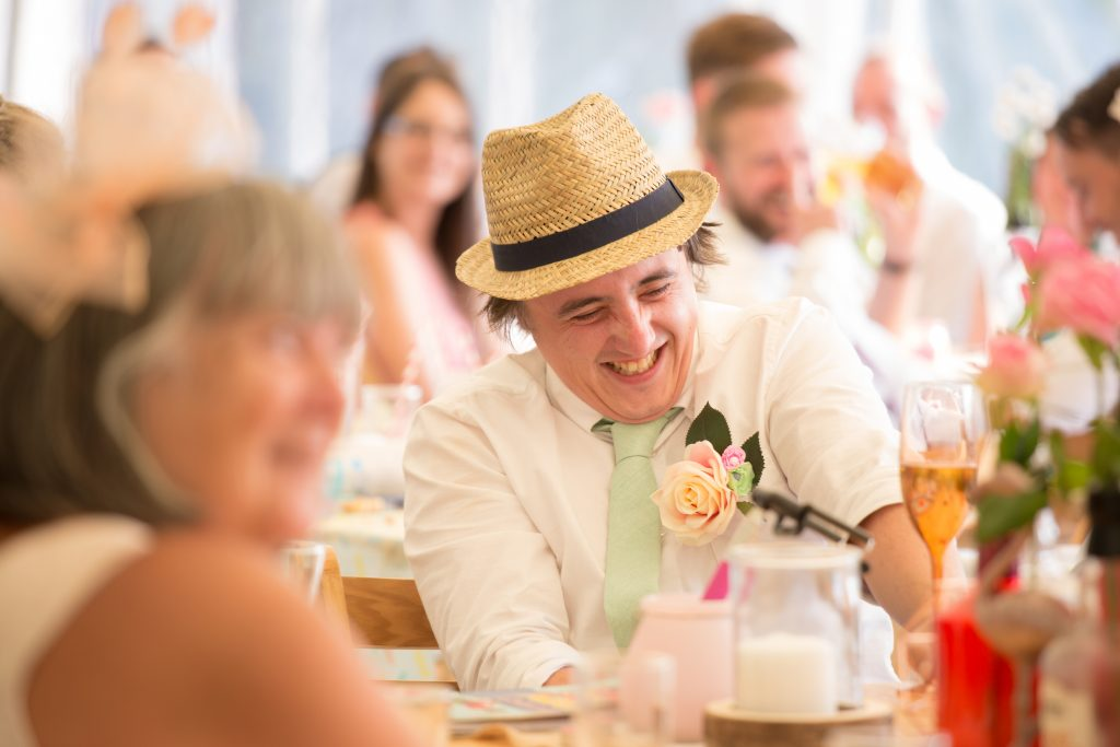 groom with straw hat laughing