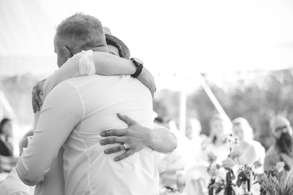 black and white photo of groom hugging best man