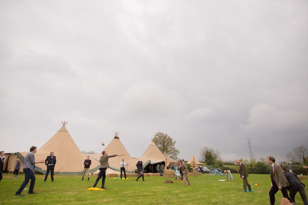 photo showing tipi in field and wedding guests playing games