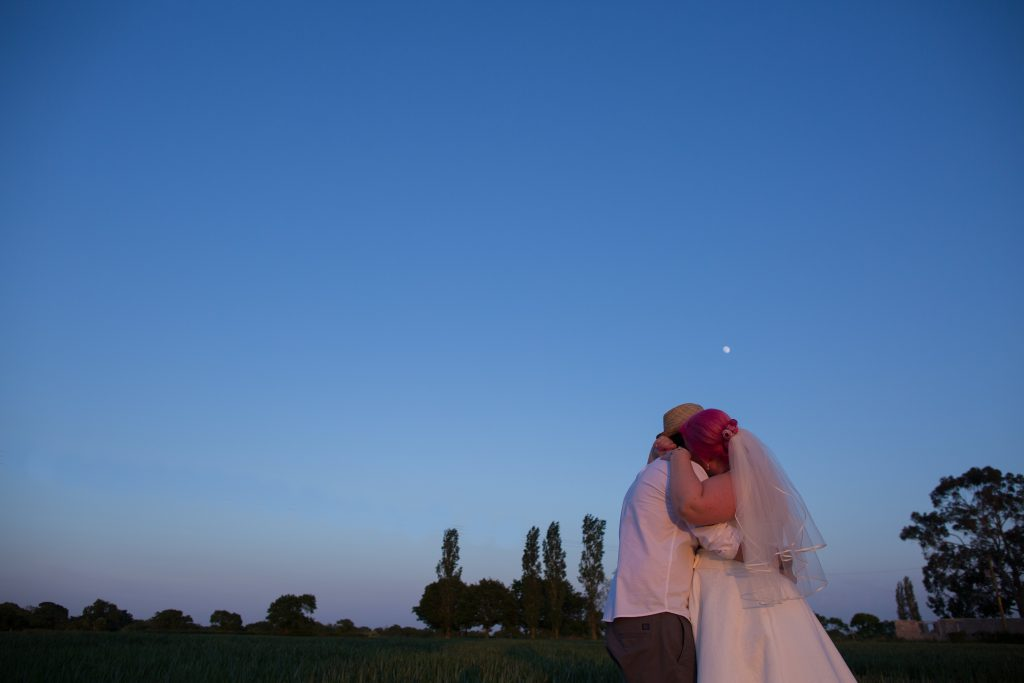 photo of bride and groom against blue sky at night