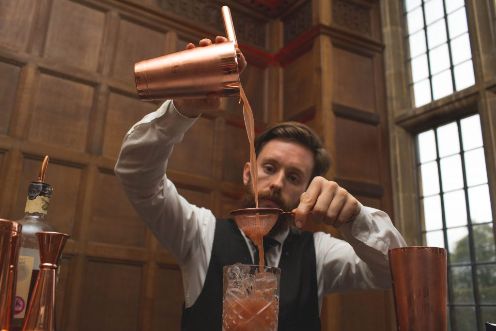 barman pouring cocktail into glass from height