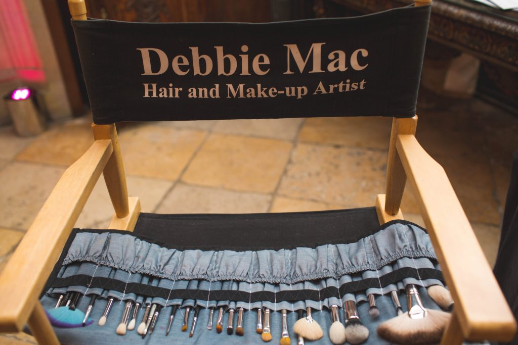 photo of make up artists chair with brushes on