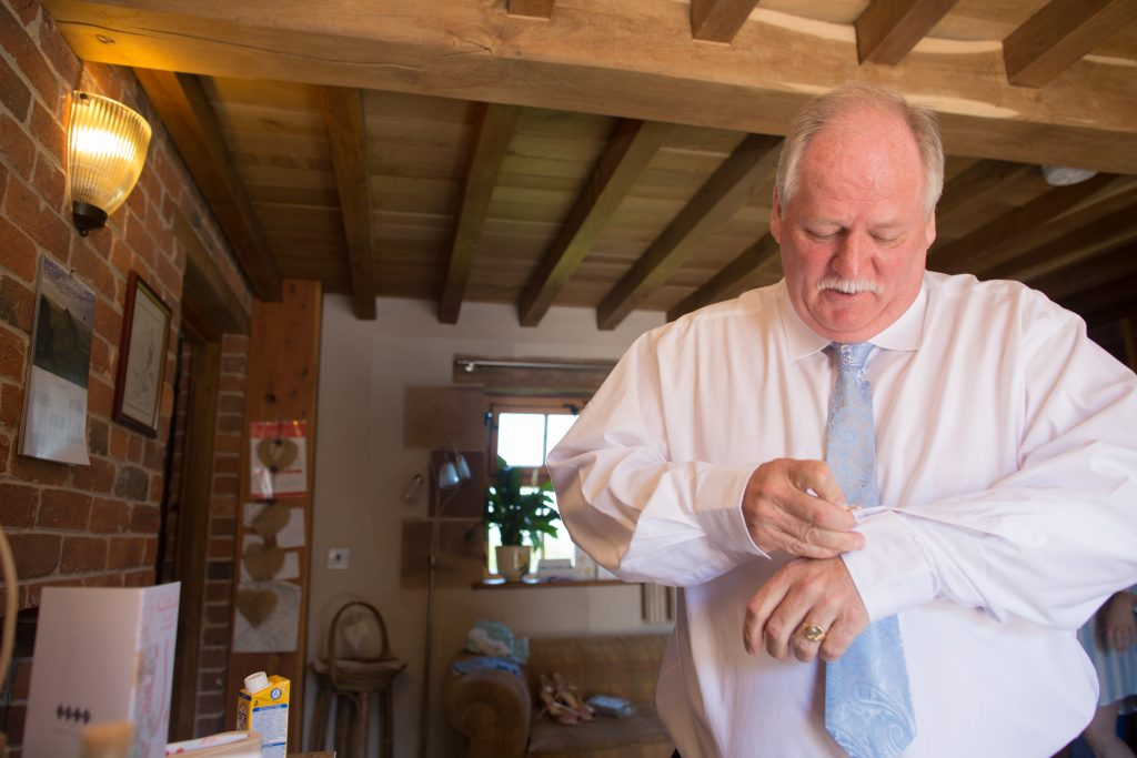 father of bride putting cufflinks on