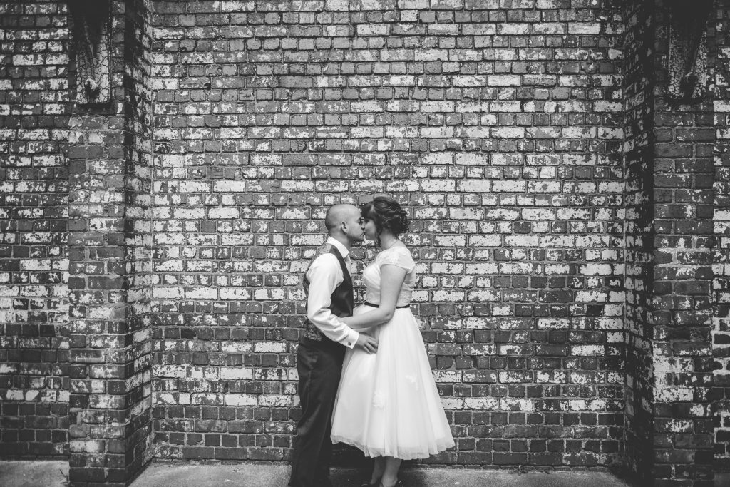 black and white photo of bride and groom kissing in front of a wall