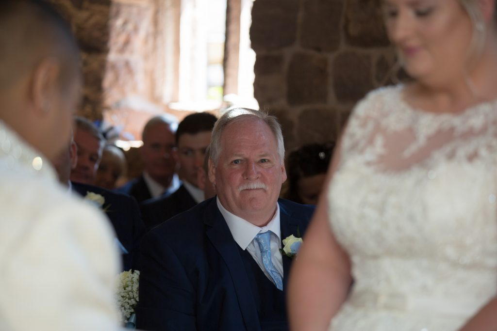 Father of the bride watching daughter get married