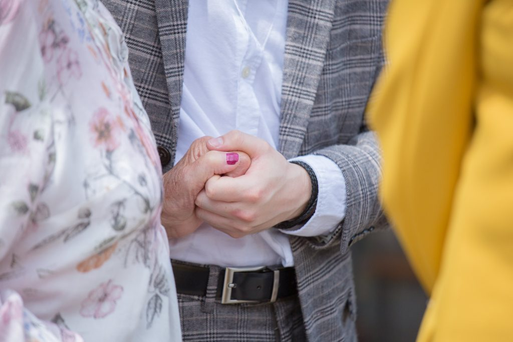 close up of wedding guest holding hand of grandma