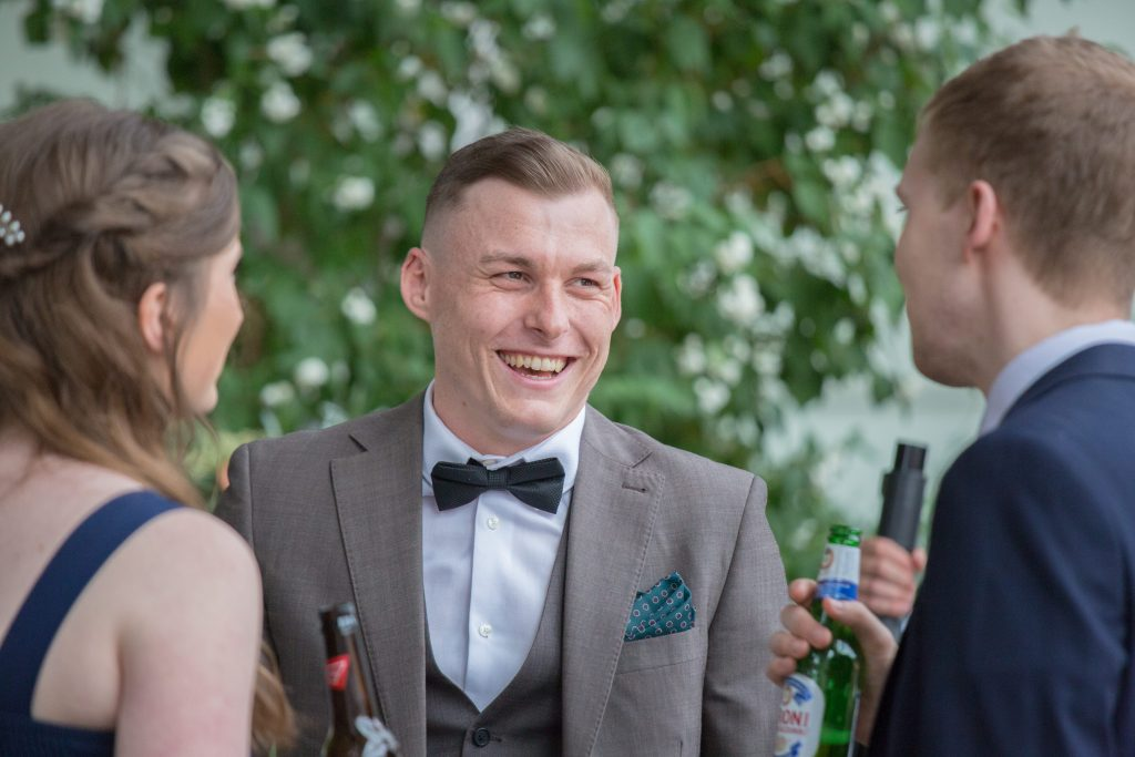 wedding guest in bowtie laughing