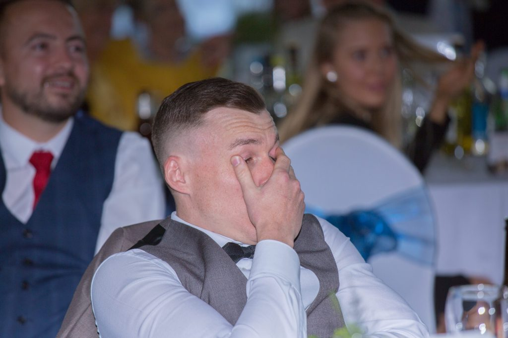 guest at wedding covering face during speeches
