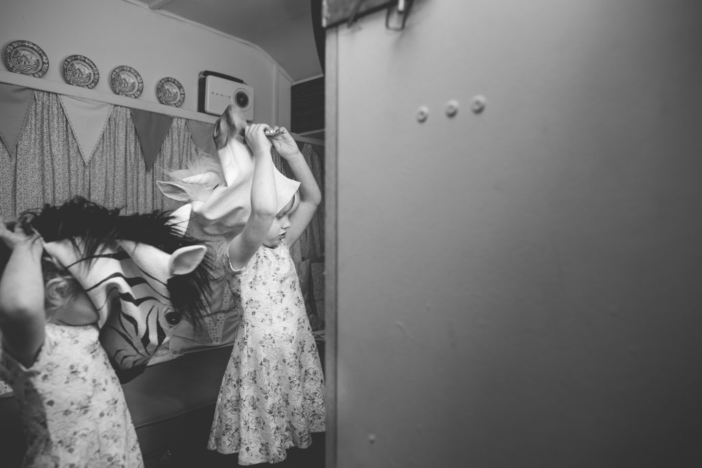black and white photo of two little girls trying on Photo Booth props