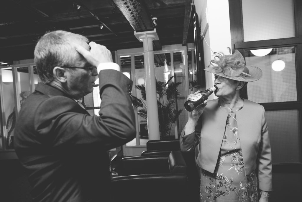 black and white photo of brides mum drinking beer