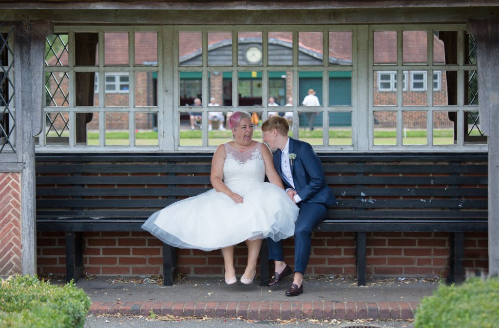 two brides sat on bench laughing