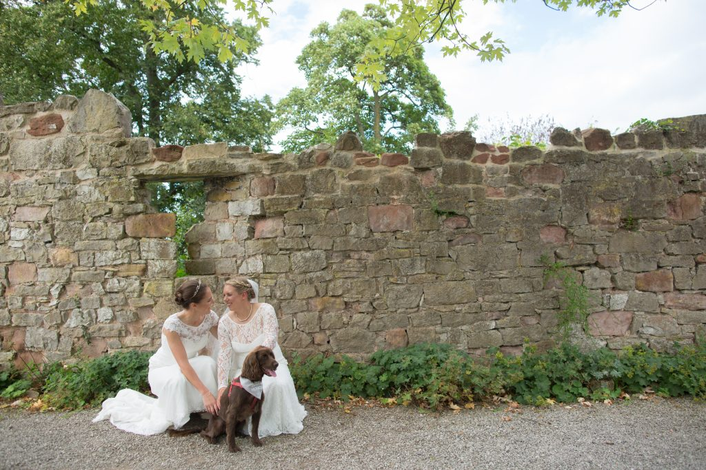 picture of two brides with their dog on wedding day