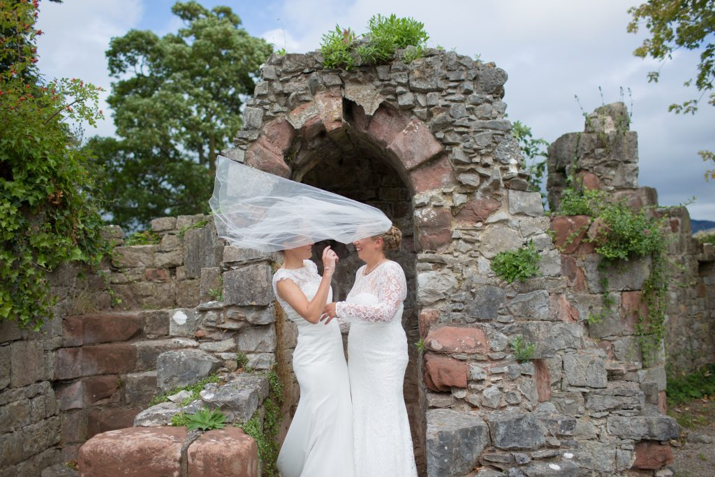 two brides in dresses with veil blowing across their faces