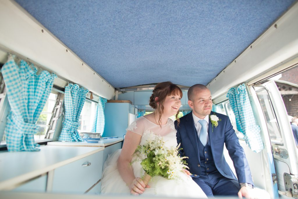photo of newly married couple sat inside a camper van