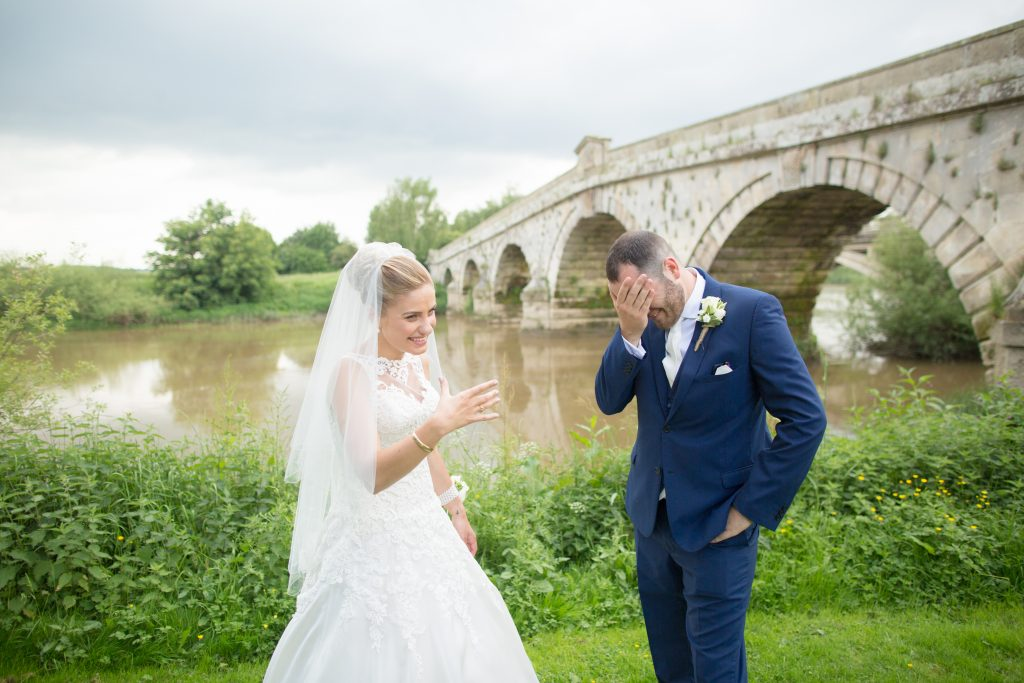 bride and groom stood by river laughing