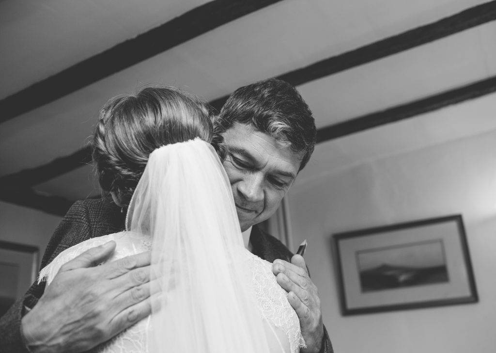 black and white photo of father of bride hugging her