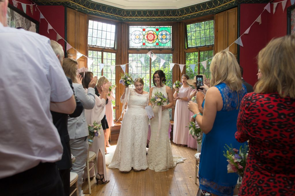 two brides in wedding dresses celebrate getting married