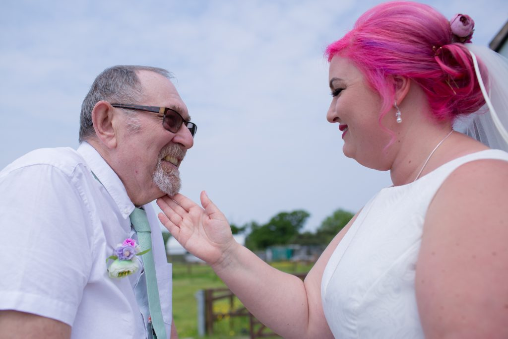 bride with pink hair touching her dads face