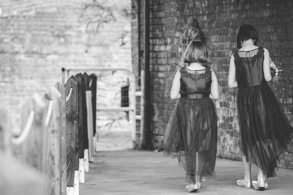 two flower girls walking by canal