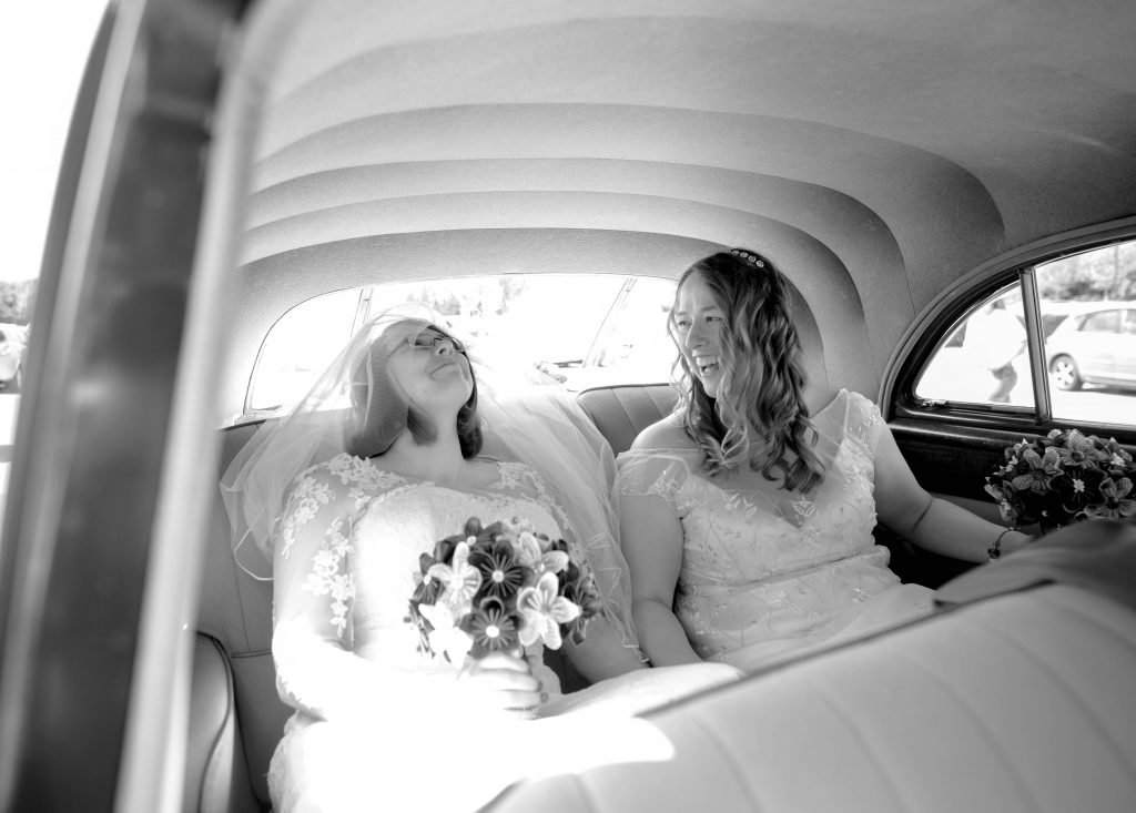black and white photo of two brides in the back of a wedding car