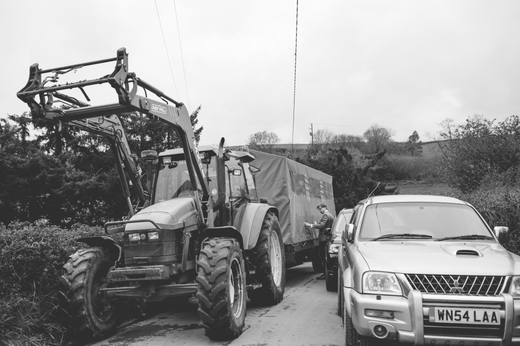 black and white photo of tractor and trailer at wedding