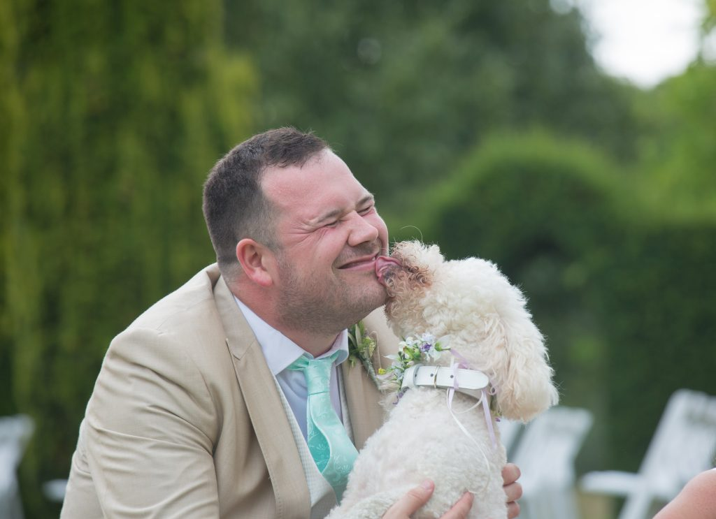 dog licking face of groom