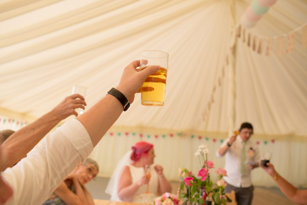 wedding guest holding drink in the air during wedding speeches