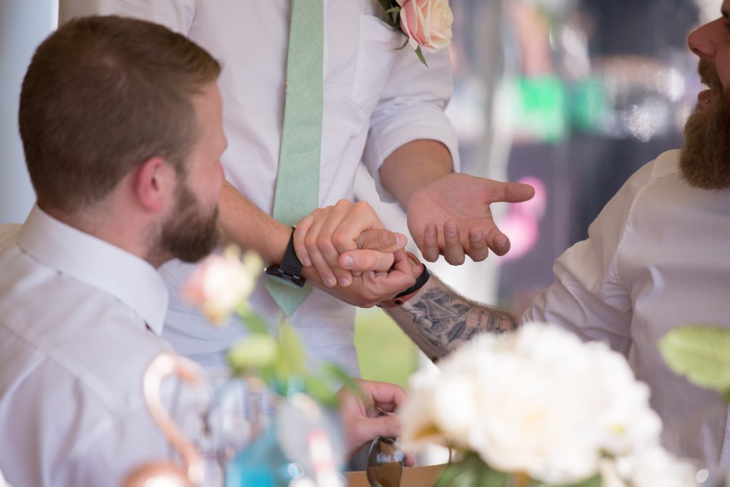 tattooed wedding guest holding grooms hand