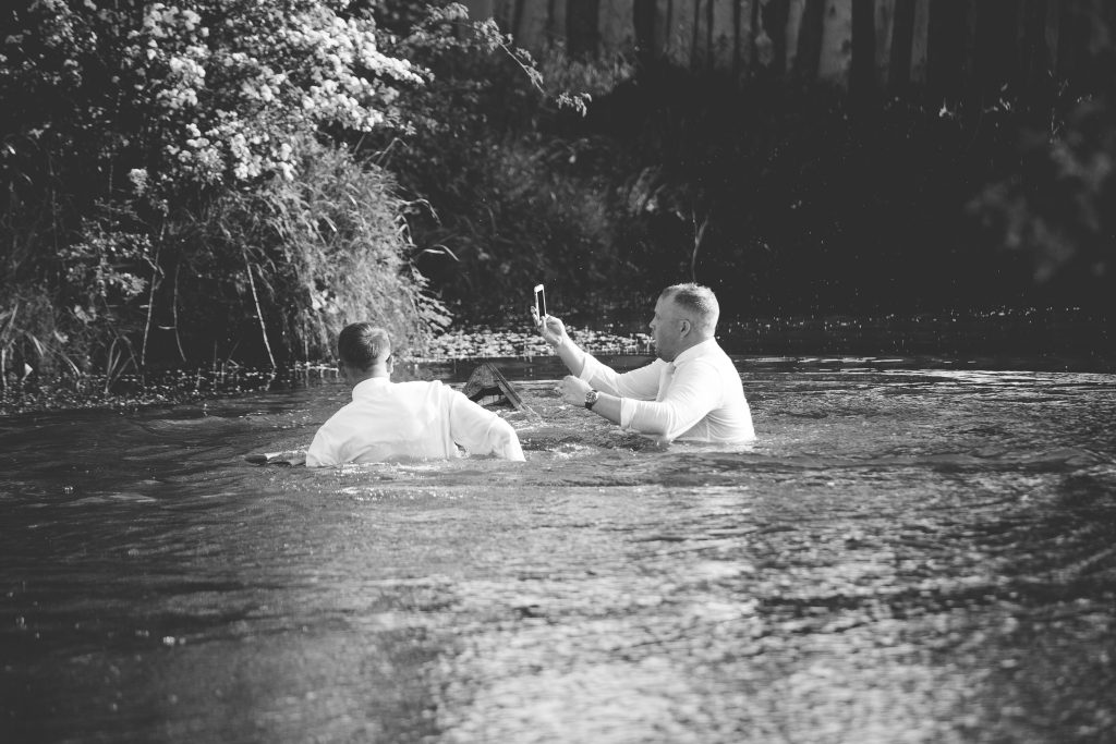 best man in pond holding mobile out of the water