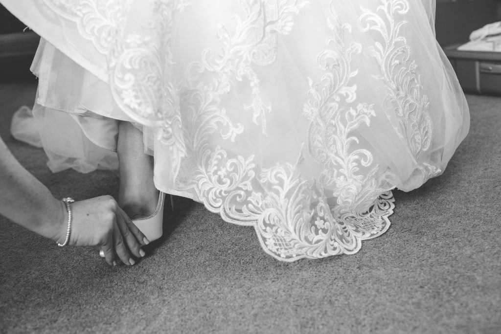 bride having help putting shoe on