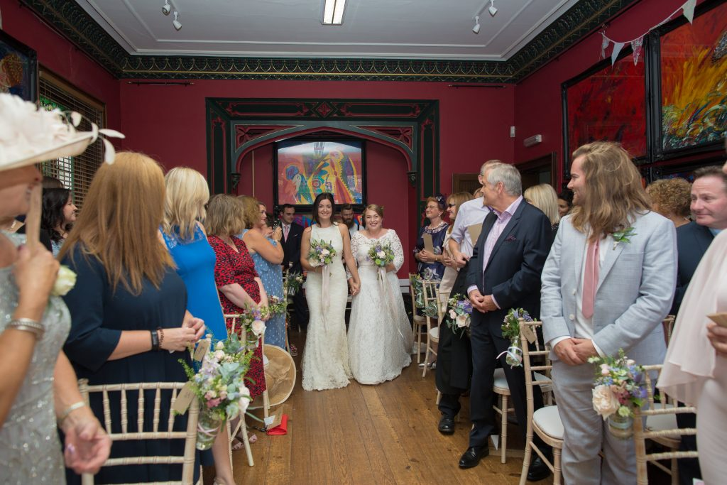 two brides enter wedding ceremony together