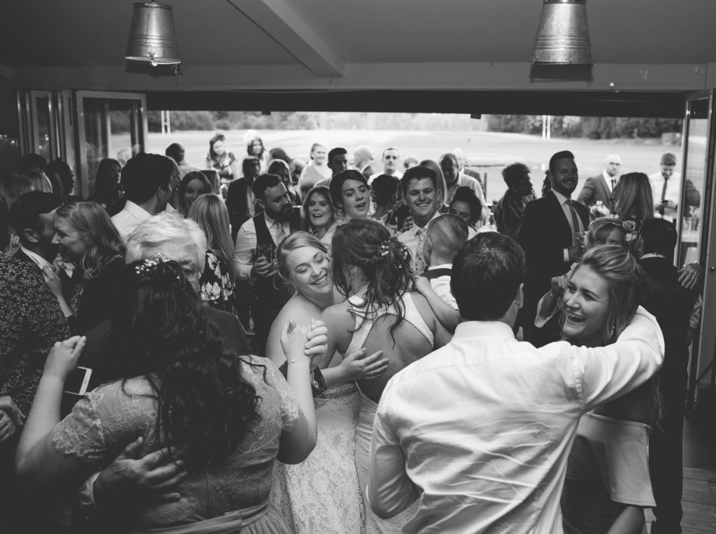 Black and white photo of two brides dancing surrounded by wedding guests
