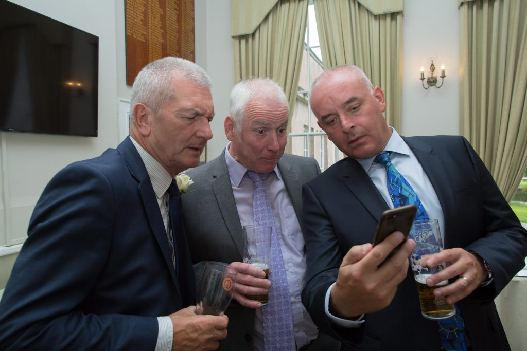 three wedding guests looking at mobile phone