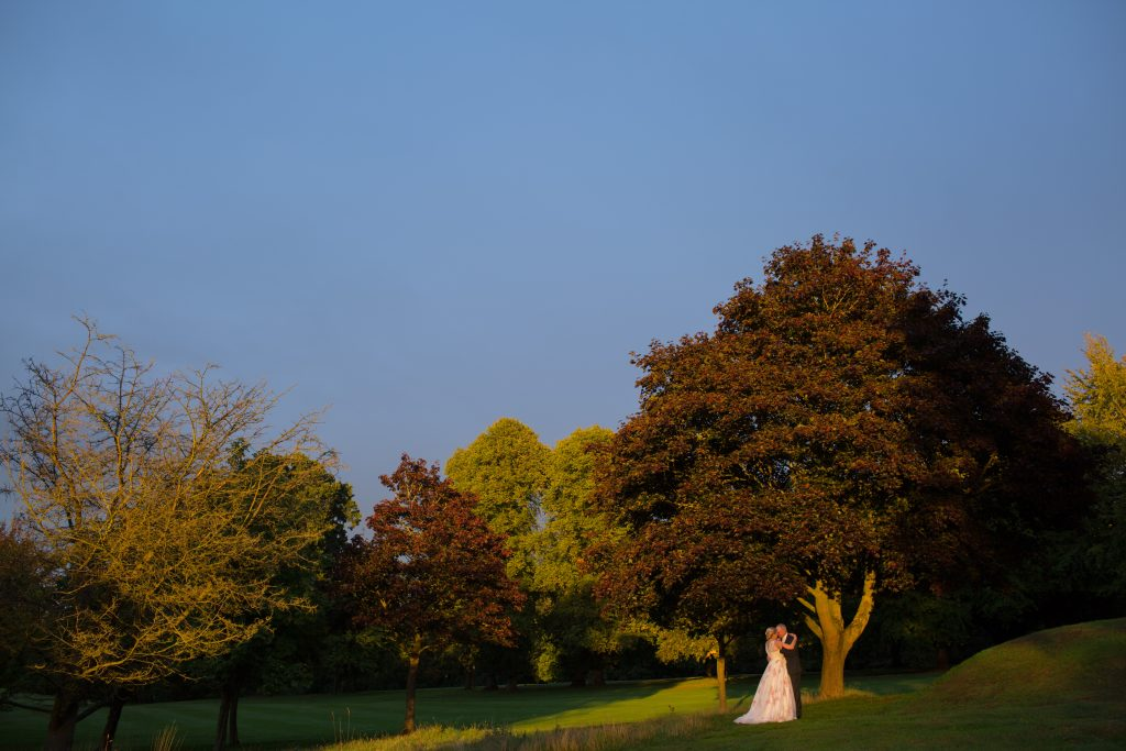 bride and groom stood in sun at Brocton Hall