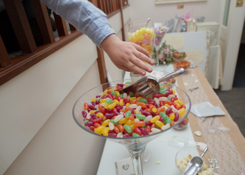 young wedding guest reaching for sweets