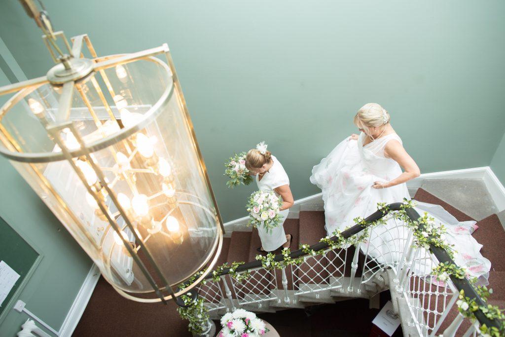 bride in wedding dress walking down staircase