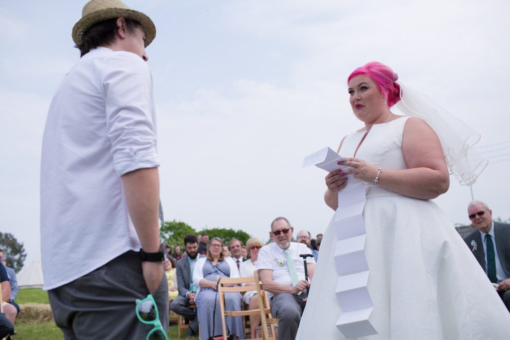 bride with pink hair reading wedding vows