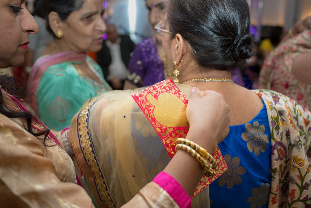 wedding guest having her sari adjusted