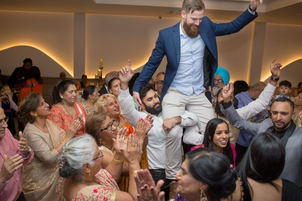groom being lifted up on shoulders