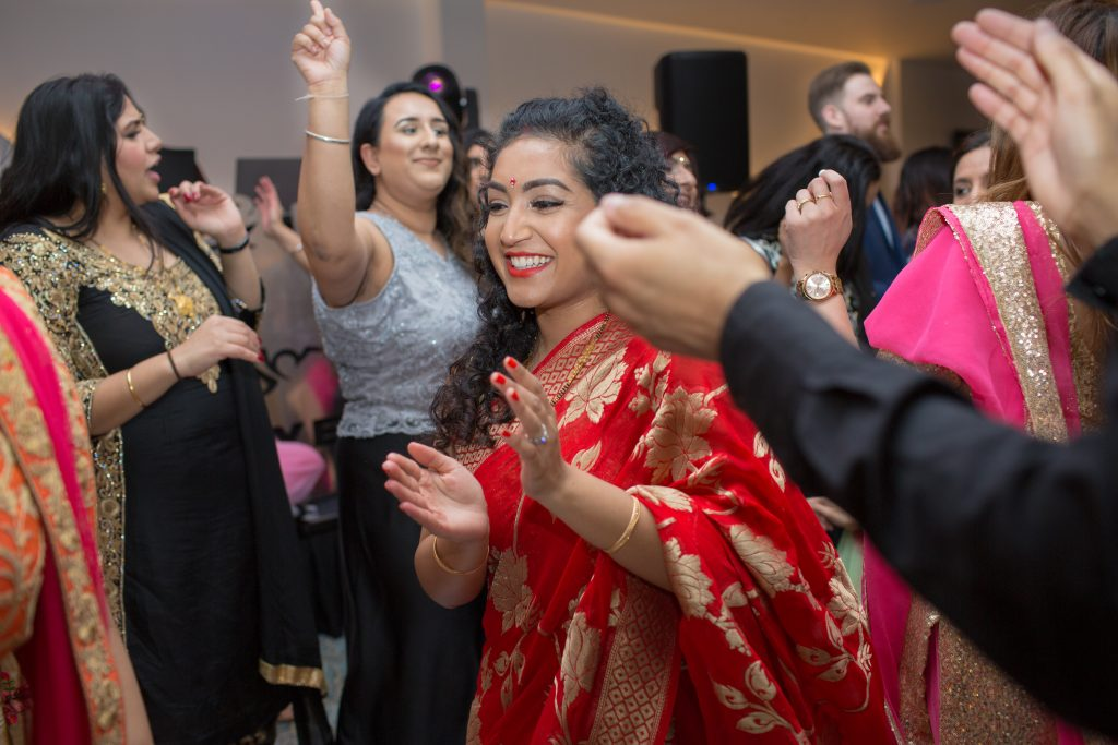 wedding guests wearing red sari dancing