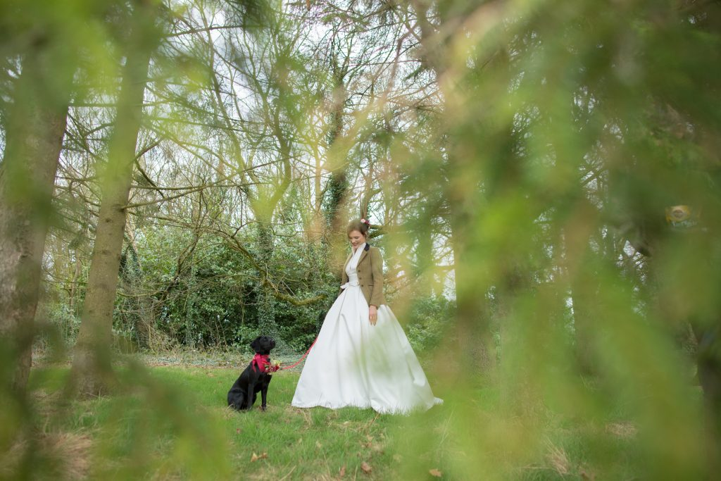 Photo of country bride with dog taken through trees