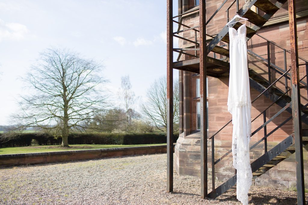 Enzoani Wedding dress hanging from metal staircase