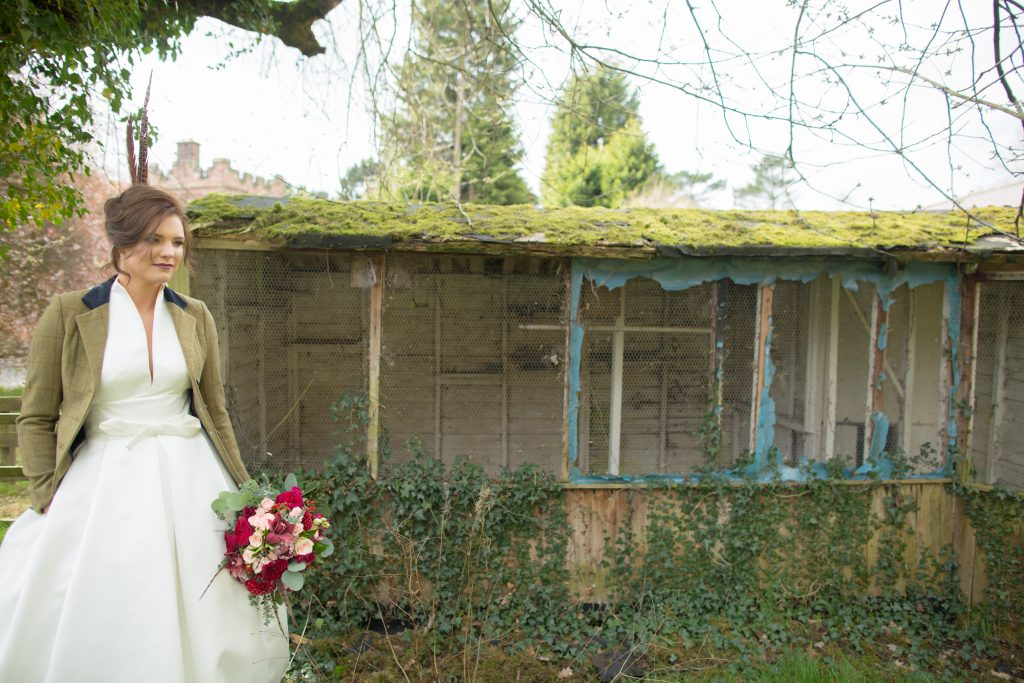 Bride stood holding bouquet next to old shed